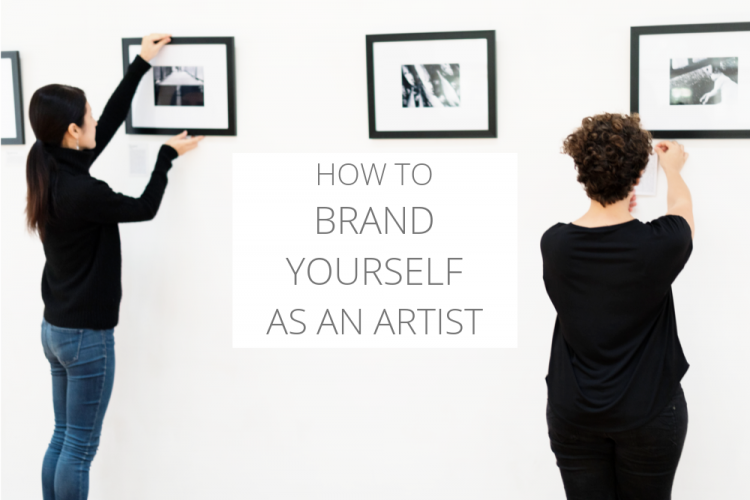 Two women hanging art on a gallery wall | How to brand yourself as an artist.