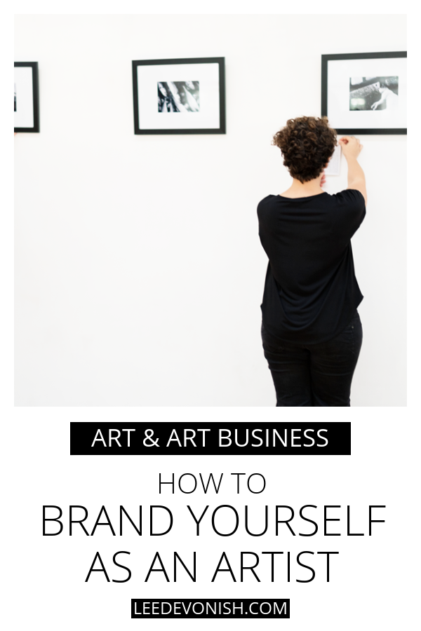 Woman hanging art on gallery wall | how to brand yourself as an artist