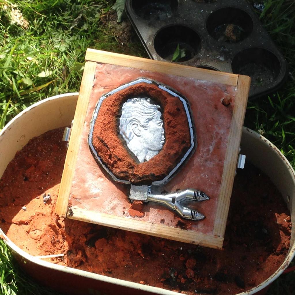Aluminium coin in casting sand